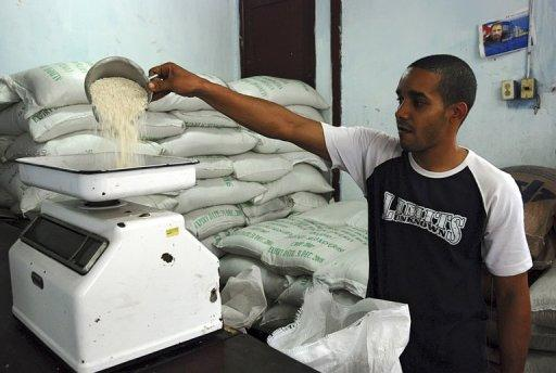 A Cuban salesman weighs rice in a shop in Havana