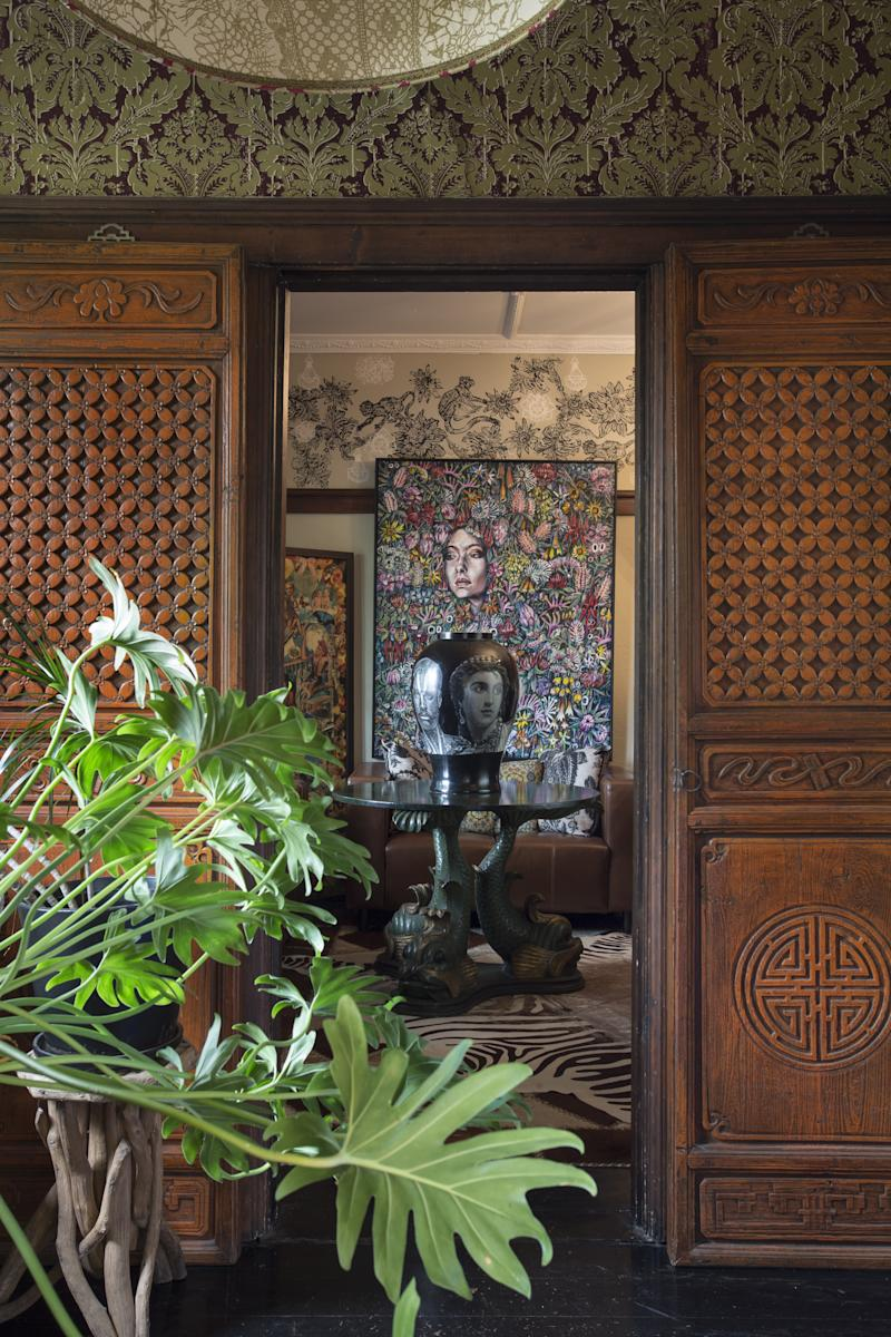 Having been forbidden to attach anything to his bedroom walls as a child, Australian textile designer Peter Curnow, an avid collector, now applies pattern and texture to every surface of his home. Walking through each room is like thumbing through the pages of a travel diary. Chinese lattice screens in the entrance area frame a large round Irish table with legs carved in the shape of dolphins, accented in gold. Anima-hide rugs cover floors and walls, and paintings by Gavin Brown, such as Wildflowers with Figure (2013), seen here, are featured in several rooms.