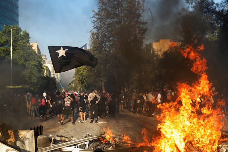 Demonstrators react behind improvised bonfire during an anti-government protest in Santiago, Chile on Oct. 28, 2019. (Photo: Pablo Sanhueza/Reuters)