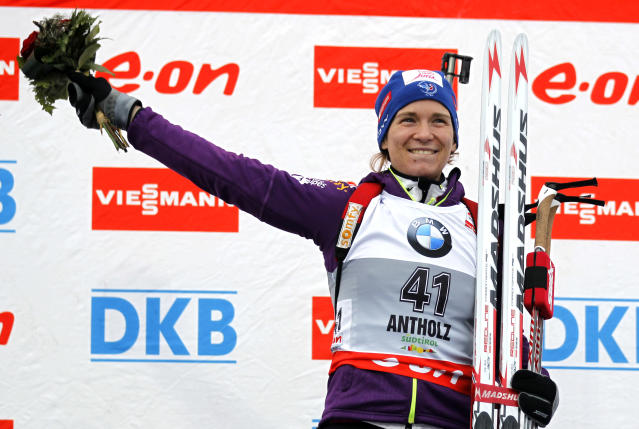 Anais Bescond, of France, celebrates on the podium after winning a women's Biathlon 7.5 kilometer sprint race in Anterselva, Italy, Thursday, Jan. 16, 2014. (AP Photo/Felice Calabro')