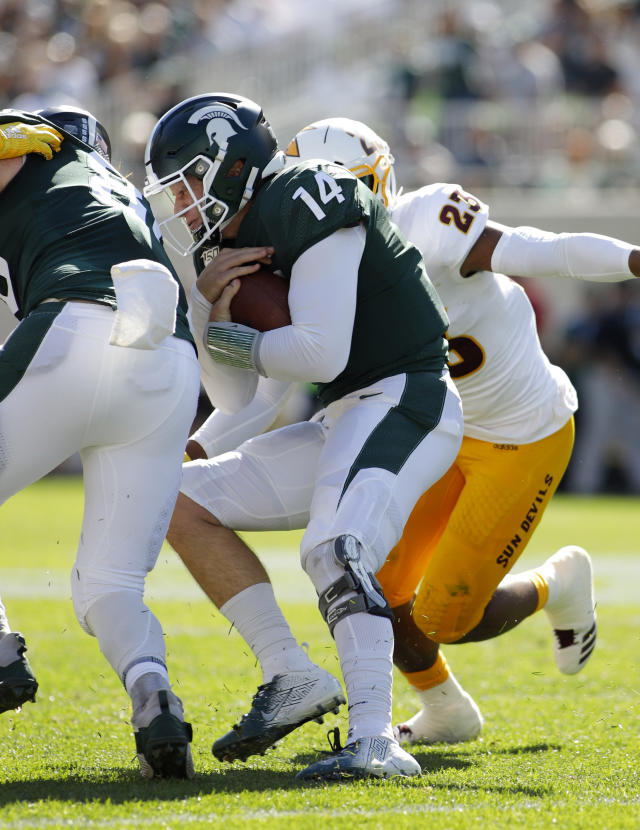 Michigan State quarterback Brian Lewerke (14) collides with teammate Matt Seybert, left, and is tackled by Arizona State's Tyler Whiley on a keeper during the first quarter of an NCAA college football game Saturday, Sept. 14, 2019, in East Lansing, Mich. (AP Photo/Al Goldis)