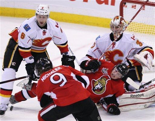 Ottawa Senators' Colin Greening collides with Calgary Flames goaltender Leland Irving (37) as Flames' Cory Sarich (6) defends against Senators' Milkan Miackalek's (9) shot during second-period NHL hockey game action in Ottawa, Ontario, Friday, Dec. 30, 2011. (AP Photo/The Canadian Press, Fred Chartrand)