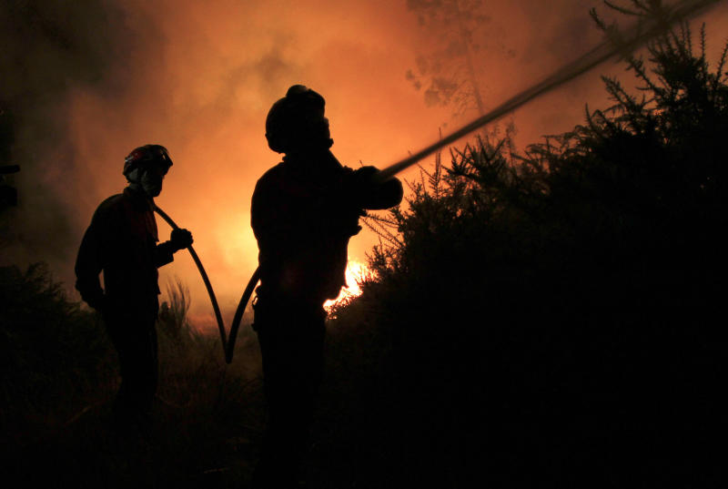 Portuguese firefighters work on a fire in Tondela, near Viseu, Portugal, Thursday night, Aug. 22, 2013. Portuguese authorities said one firefighter has died and six were injured as they battled a wildfire in Tondela. (AP Photo/Francisco Seco)