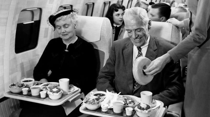 Black and white photo of man and woman receiving elaborate meal on plane