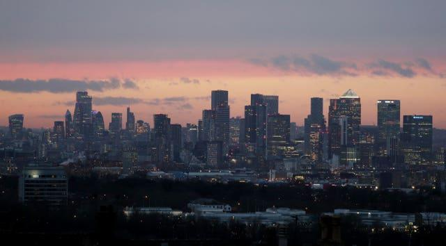 Canary Wharf and the City of London skyline at sunset as seen from Shooters Hill, London (Jonathan Brady/PA)