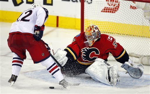 Columbus Blue Jackets' Vinny Prospal, left, from the Czech Republic, has the puck knocked away by Calgary Flames goalie Joey MacDonald during the third period of an NHL hockey game Friday, March 29, 2013, in Calgary, Alberta. Columbus won 6-4. (AP Photo/The Canadian Press, Jeff McIntosh)