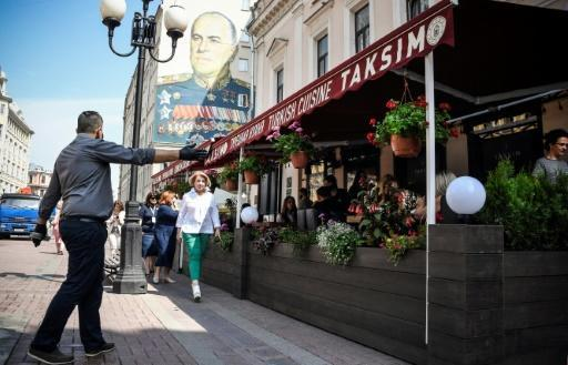 Soviet WWII commander Marshal Georgy Zhukov looks down as cafe owners hustle for business in Moscow, prompting suggestions that the easing of lockdown has come too early