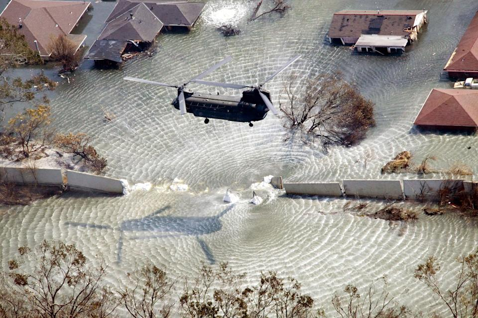A Chinook helicopter on Sept. 11, 2005, flies in sandbags to plug a levee break from Hurricane Katrina in the Gentilly neighborhood of New Orleans.