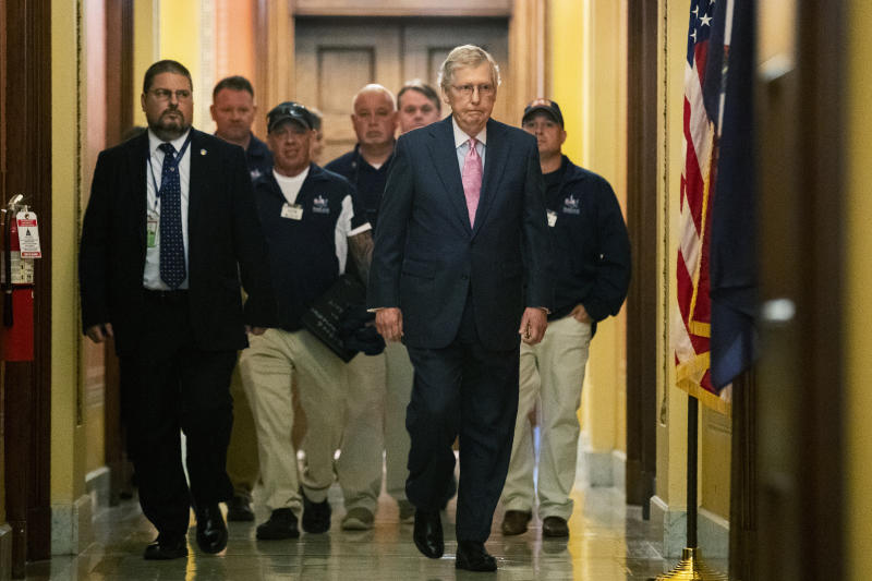 Senate Majority Leader Mitch McConnell walks with Sept. 11 first responders John Feal, second from left, Ret. Lt. Michael O'Connell, back right, and other first responders, following their meeting at McConnell's office on Capitol Hill in Washington, Tuesday, June 25, 2019. (AP Photo/Manuel Balce Ceneta)