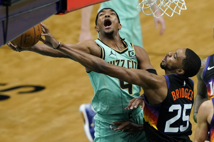 Phoenix Suns forward Mikal Bridges blocks a shot by Charlotte Hornets guard Devonte' Graham during the first half of an NBA basketball game on Sunday, March 28, 2021, in Charlotte, N.C. (AP Photo/Chris Carlson)