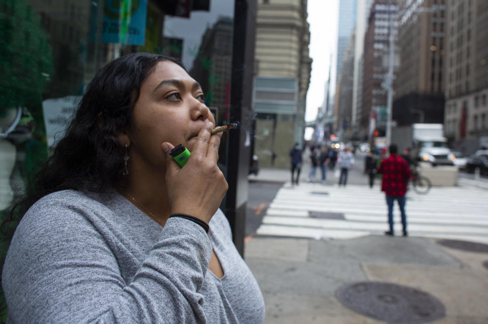 Eliana Miss Illi, General Manager of Weed World poses as she smokes a joint on 7th Avenue in Midtown New York City, March 31, 2021. - New York Governor Andrew Cuomo signed legislation legalizing recreational marijuana on March 31. 2021, with a large chunk of tax revenues from sales set to go to minority communities. New York joins 14 other US states and the District of Columbia in permitting cannabis after lawmakers in both state chambers, where Cuomo's Democratic Party holds strong majorities, backed the bill on March 30. (Photo by Kena Betancur / AFP) (Photo by KENA BETANCUR/AFP via Getty Images)