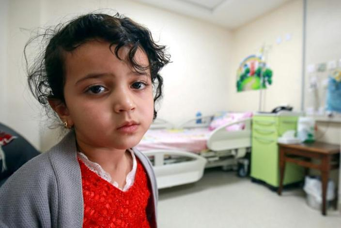 Yemeni patient Manal, who can not move her right arm since birth, waits for her medical checkup (AFP Photo/Khalil MAZRAAWI)