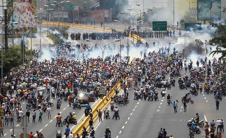 Demonstrators clash with riot police while ralling against Venezuela's President Nicolas Maduro's government in Caracas