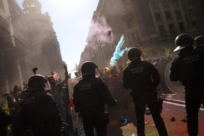 Demonstrators throw a can of beer and power painting at Catalan police officers during clashes with pro independence protesters on their way to meet demonstrations of members and supporters of National Police and Guardia Civil in Barcelona on Saturday, Sept. 29, 2018. (AP Photo/Emilio Morenatti)