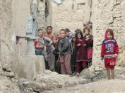 Internally displaced Afghan children looking on next to their shelters on the outskirts of Kabul