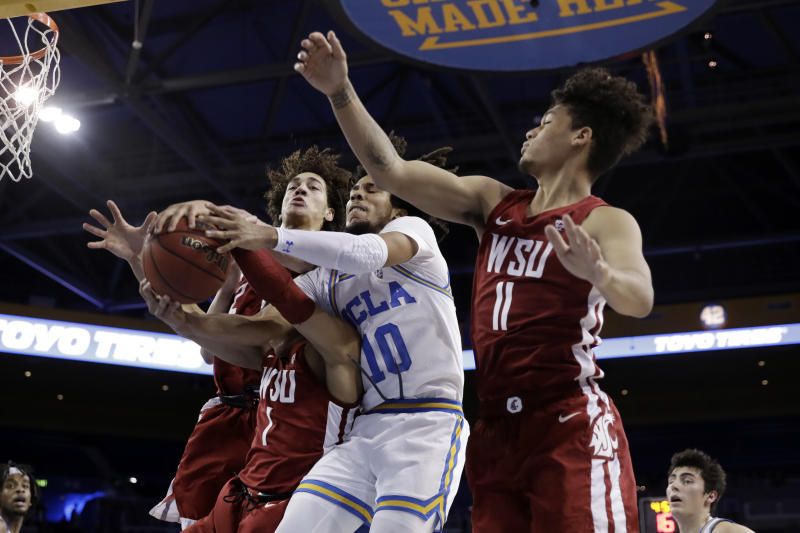 UCLA guard Tyger Campbell (10) vies for a rebound against Washington State guard Jervae Robinson (1) and forward DJ Rodman (11) during the first half of an NCAA college basketball game Thursday, Feb. 13, 2020, in Los Angeles. (AP Photo/Marcio Jose Sanchez)