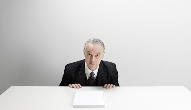 Worried businessman at desk with blank paper