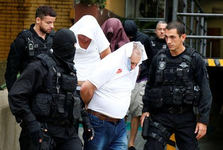 """People detained during the probe known as """"Operation Weak Flesh"""" are escorted by police officers as they leave the Institute of Forensic Science in Curitiba, Brazil March 17, 2017. REUTERS/Rodolfo Buhrer"""