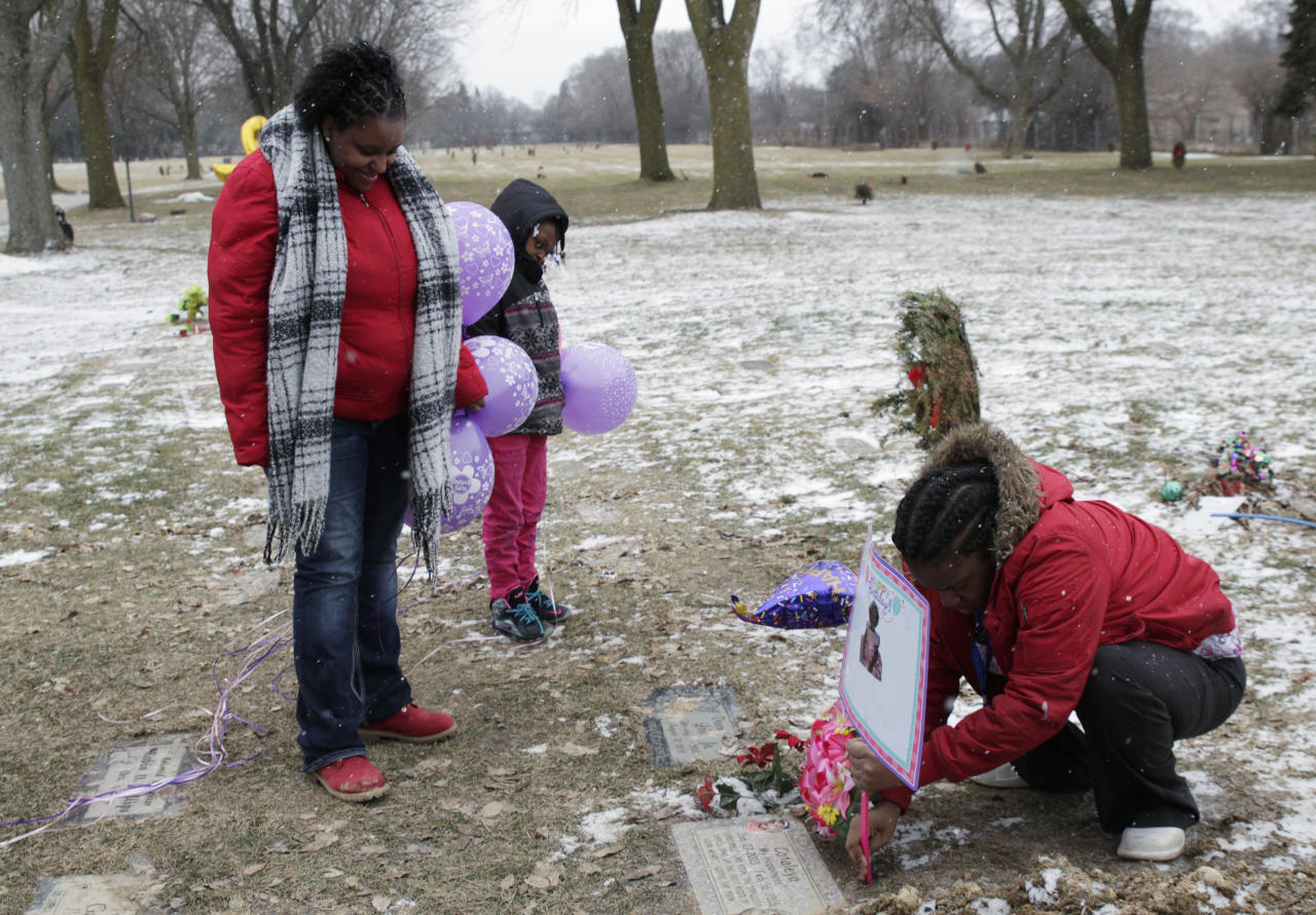 In this Jan. 27, 2017, Helen Jackson, left, along with her daughter Raniah Ricks, center, and Brittany Blake visit the grave of Jackson's daughter Cataleya Tamekia-Damiah Wimberly. Wimberly died at the age of 1 in Feb. 2016 from a methadone overdose in a case the Milwaukee police are still investigating. The number of children's deaths is still small relative to the overall toll from opioids, but toddler fatalities have climbed steadily over the last 10 years. (AP Photo/Carrie Antlfinger)