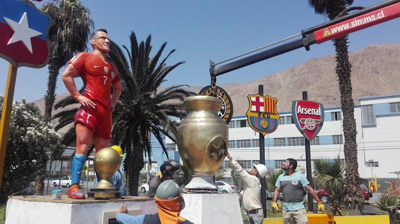 Standing Tall | The giant statue features the Chile star alongside the crests of his former clubs and Arsenal: Twitter/TocopillaOnline