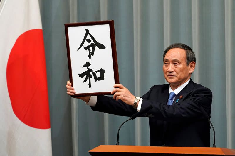 Japan's Chief Cabinet Secretary Yoshihide Suga unveils 'Reiwa' as the new era name at the prime minister's office in Tokyo