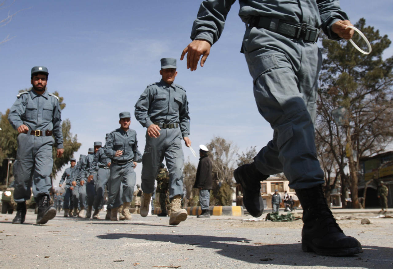 Afghan policemen run towards an anti-U.S. demonstration in Mehterlam, Laghman province east of Kabul, Afghanistan, Saturday, Feb. 25, 2012. Protesters threw rocks at police, government buildings and a U.N. office in eastern Afghanistan on Saturday, kicking off a fifth day of riots sparked by the burning of Qurans at a U.S. base, officials said. (AP Photo/Rahmat Gul)
