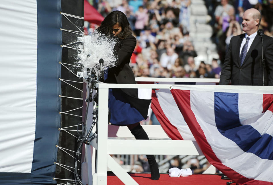 <p>The first lady job isn't all responsibility — it's also fun! The first lady wore suede black boots, a royal blue dress, and a black blazer coat to smash a bottle on a big ship</p>