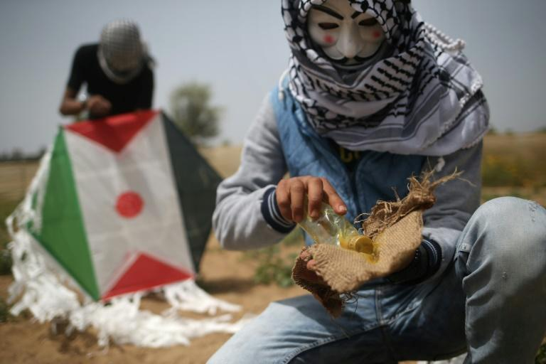 Palestinian protestors in Gaza prepare an incendiary kite before trying to fly it over the border fence with Israel on April 20, 2018