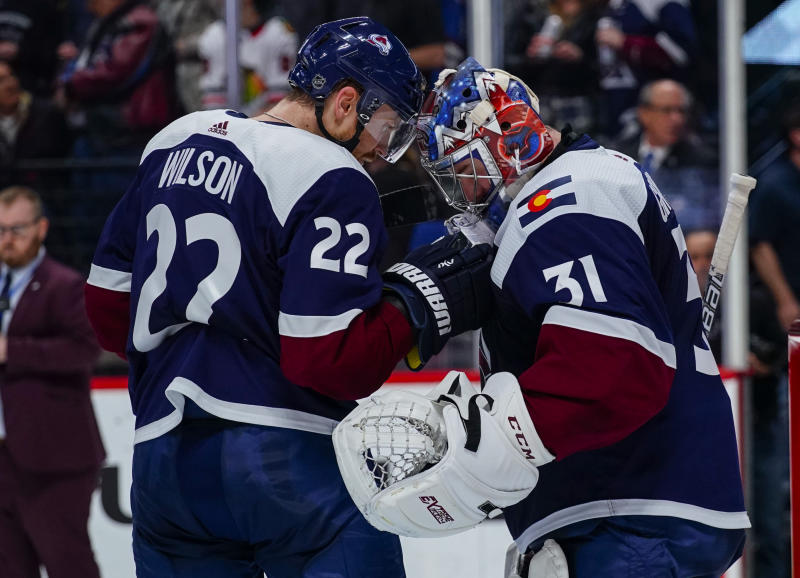 Colorado Avalanche center Colin Wilson (22) and Philipp Grubauer (31) bump heads to celebrate the team's win over the Chicago Blackhawks following an NHL hockey game, Saturday, March 23, 2019 in Denver. (AP Photo/Jack Dempsey)