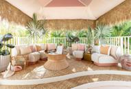 "<p><strong>Who needs a cocktail bar when you can create a dreamy getaway on your patio? </strong>For her ""Bar Mustique,"" Kavanaugh looked to natural materials to evoke a laid-back, beachy feel. A pink tented ceiling (created with Associated Interior Design Services and David Sutherland Showroom) casts a rosy glow, while its leafy trim catches the ocean breeze. One Mai Tai, please! <br></p>"
