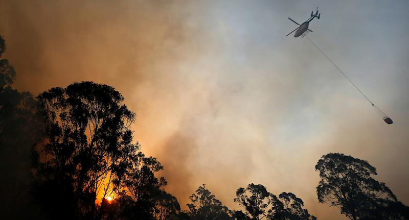 Photo shows water about to be dropped on fire in NSW by helicopter.