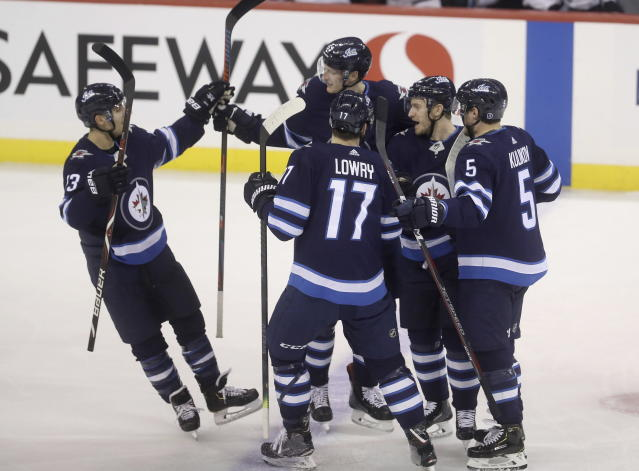 Winnipeg Jets' Brandon Tanev (13), Tyler Myers (57), Adam Lowry (17), Bryan Little (18) and Dmitry Kulikov (5) celebrate after Little scored against the San Jose Sharks' during the first period of an NHL hockey game in Winnipeg, Manitoba, Tuesday, March 12, 2019. (Trevor Hagan/The Canadian Press via AP)