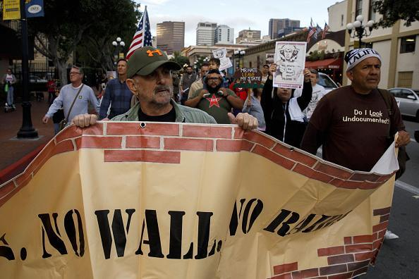 "Demonstrators march with a border wall sign during a protest ahead of a visit by President Donald Trump in downtown San Diego, Calif., on Monday, March 13, 2018. Trump is headed to the heart of ""the resistance"" —California, a state that remains the anchor of the U.S. economy even as it has become the forefront of opposition to his presidency. Photographer: Patrick T. Fallon/Bloomberg"