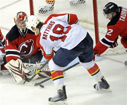 Florida Panthers' Shawn Matthias (18) attempts to score past New Jersey Devils goaltender Johan Hedberg, left, of Sweden, as Devils' Matt Taormina (32) defends during the second period of an NHL hockey game, Friday, Jan. 6, 2012, in Newark, N.J. (AP Photo/Bill Kostroun)