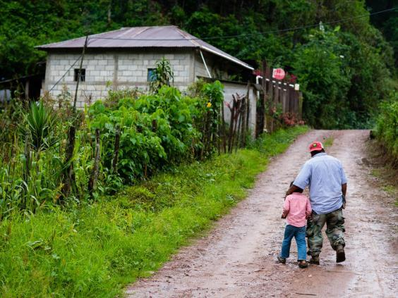 Rodrigo Carrillo and his five-year-old son walk up the dirt road in Hoja Blanca (Sarah L Voisin/Washington Post)