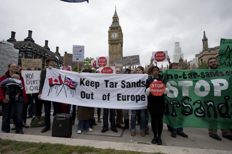 """Demonstrators pose with their banners for the media as they take part in an anti-tar sands protest outside the Houses of Parliament in London, timed to coincide with Canadian Prime Minister Stephen Harper addressing the British Parliament ahead of the G-8 summit, Thursday, June 13, 2013.  Harper is the first sitting Canadian prime minister to formally address the British Parliament since the Second World War, when William Lyon Mackenzie King spoke in Westminster's Royal Gallery only weeks before D-Day.   Harper thanked British Prime Minister David Cameron for his """"robust advocacy"""" on behalf of a free-trade pact between Canada and the European Union during his address Thursday in London to British lawmakers.  (AP Photo/Matt Dunham)"""