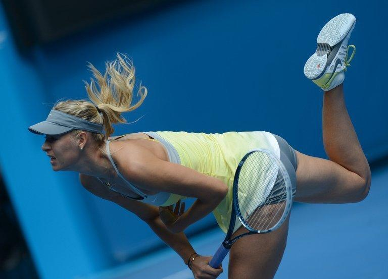 Maria Sharapova serves to Olga Puchkova on the first day of the Australian Open in Melbourne on January 14, 2013