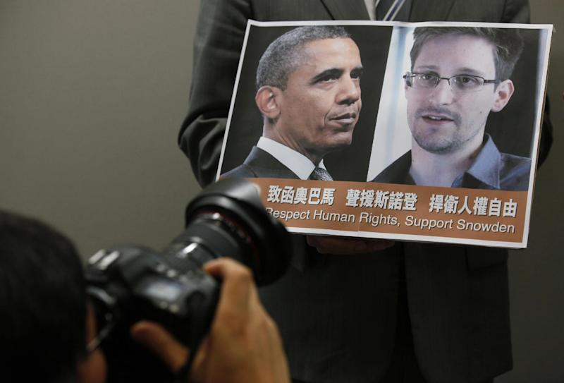 FILE - In this June 14, 2013 file photo, a photographer takes picture of President Barack Obama and Edward Snowden held by pro-democractic legislator Gary Fan Kwok-wai during a news conference in Hong Kong. Whisked out of a luxury Hong Kong hotel, vanishing into a mysterious wing of the Moscow airport, Edward Snowden's continent-jumping, hide-and-seek game seems like the stuff of a pulp thriller _ a desperate man's drama played out before a worldwide audience trying to decide if he's a hero or a villain. But the search for the former National Security Agency contractor who spilled government secrets has become something of a distracting sideshow, some say, overshadowing at least for now the important debate over the government's power to seize the phone and Internet records of millions of Americans to help wage the war on terrorism. (AP Photo/Kin Cheung, File)