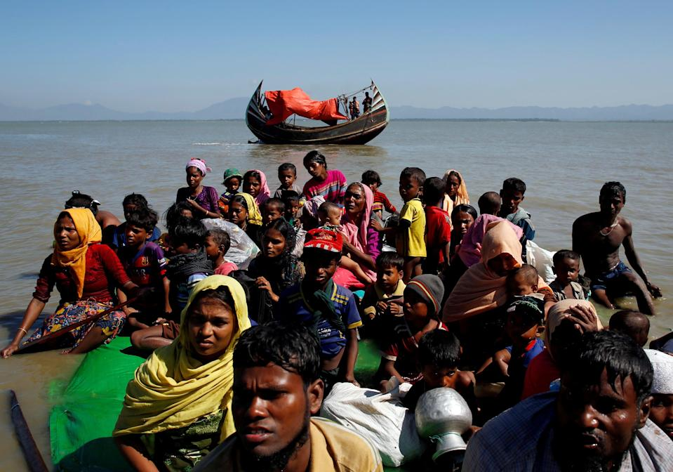 <p>Rohingya refugees sit on a makeshift boat as they are interrogated by the Bangladeshi border guard after crossing the Bangladesh-Myanmar border, at Shah Porir Dwip near Cox's Bazar</p> (REUTERS)