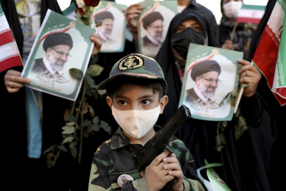 An Iranian kid holds a toy gun as he participate the victory ceremony of Iranian president-elect Ebrahim Raisi after he won the presidential election in Tehran, Iran, Saturday, June 19, 2021. Initial results released Saturday propelled Raisi, a protege of the country's supreme leader, into Tehran's highest civilian position. The vote appeared to see the lowest turnout in the Islamic Republic's history. (AP Photo/Ebrahim Noroozi)