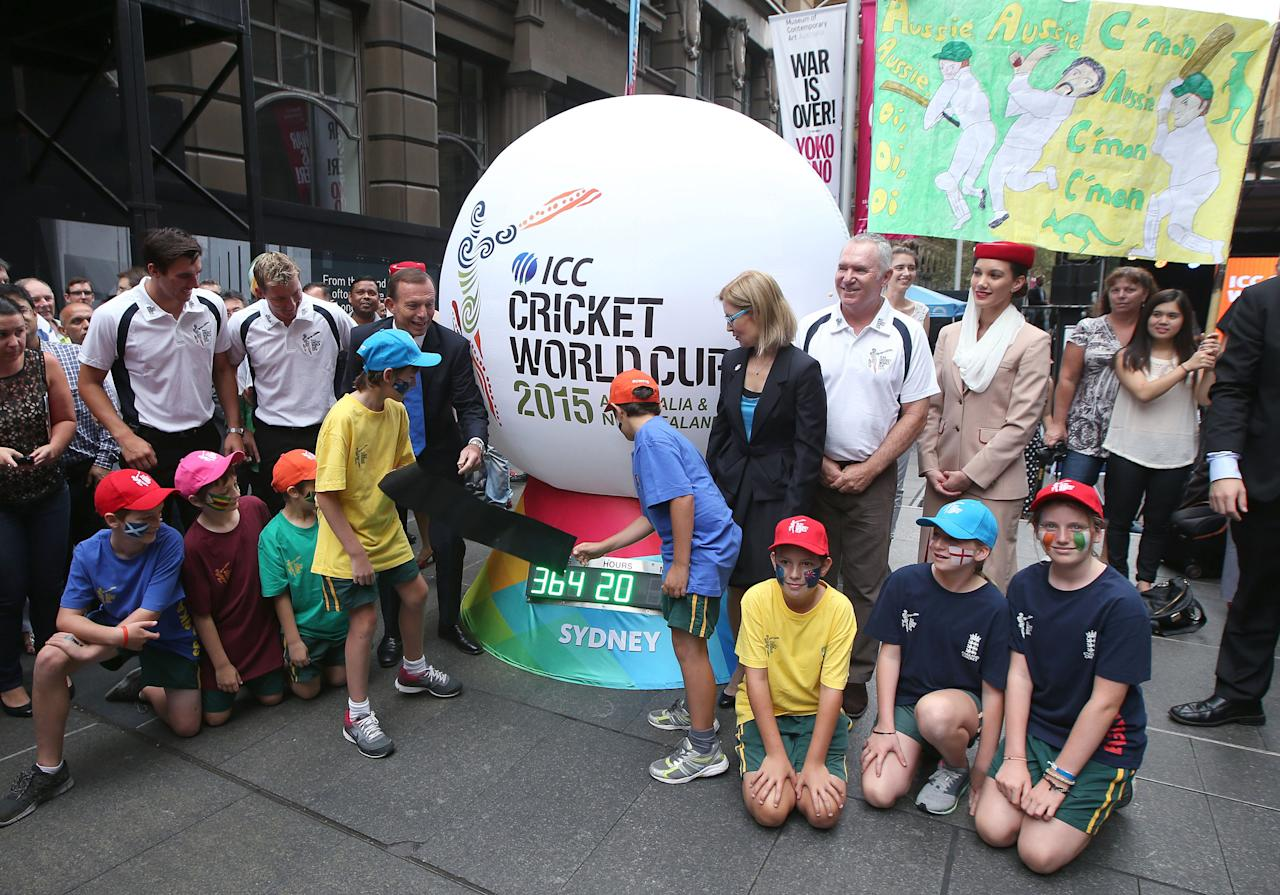 Australian Prime Minister Tony Abbott, back center left, and two children unveil a countdown clock during a ceremony in Sydney, Friday, Feb. 14, 2014, marking one year to the start of the 2015 ICC World Cup Cricket tournament. Organizers are expecting more than one million people to attend the 49 matches in Australia and New Zealand starting on Feb. 14, 2015. (AP Photo/Rick Rycroft)