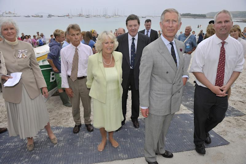 The Prince of Wales with The Duchess of Cornwall, who has taken her shoes off, look at information about the heritage of the boat club during their visit to the Gig Boat Club at Porthmellon, St Mary's, Isles of Scilly. (Photo by Ben Birchall - PA Images/PA Images via Getty Images)