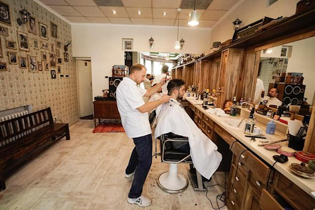 <p>Barber gets low for a haircut at a barbershop in Belgrade, Republic of Serbia. </p>