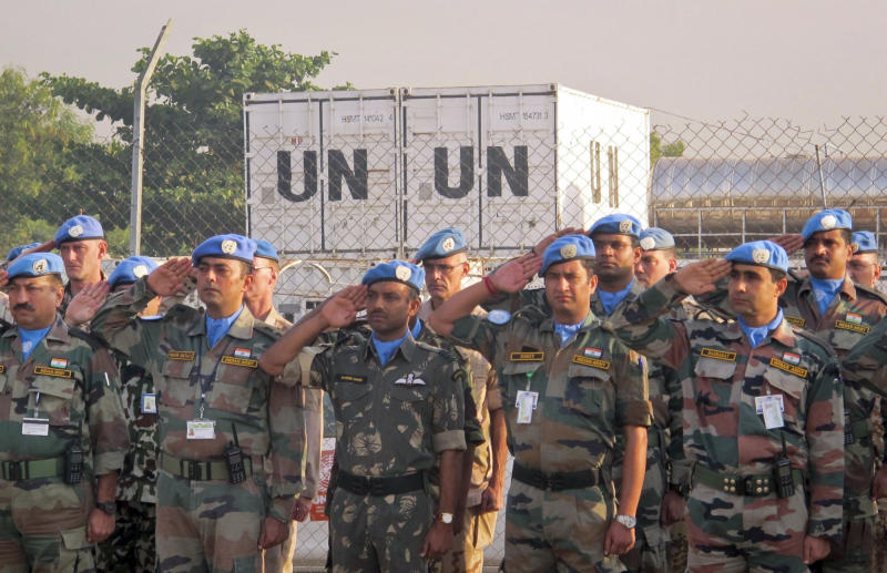 In this photo released by the United Nations Mission in South Sudan (UNMISS), U.N. peacekeepers salute during a memorial service for their two colleagues who were killed on Thursday, in the UNMISS compound in Juba, South Sudan Saturday, Dec. 21, 2013. The U.N. peacekeeping mission strongly condemned the unprovoked attack on a U.N. base in Akobo in Jonglei state, near the Ethiopian border, on Thursday that killed two Indian peacekeepers and injured a third. (AP Photo/UNMISS)