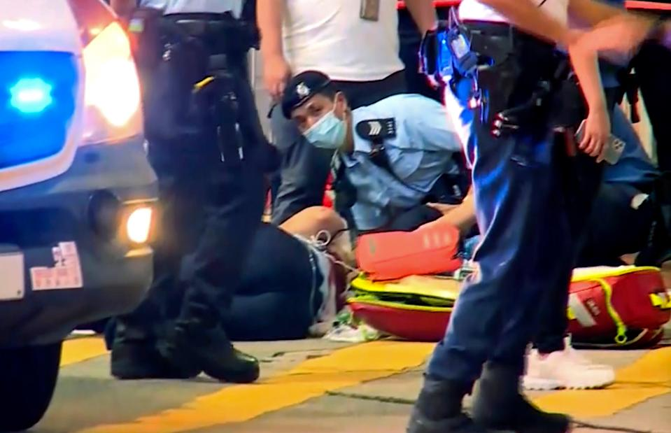 In this image from video provided by TVB, a police officer on the ground receives medical treatment after being stabbed by a man on a street in Causeway Bay of Hong Kong, 1 July 2021 (AP)