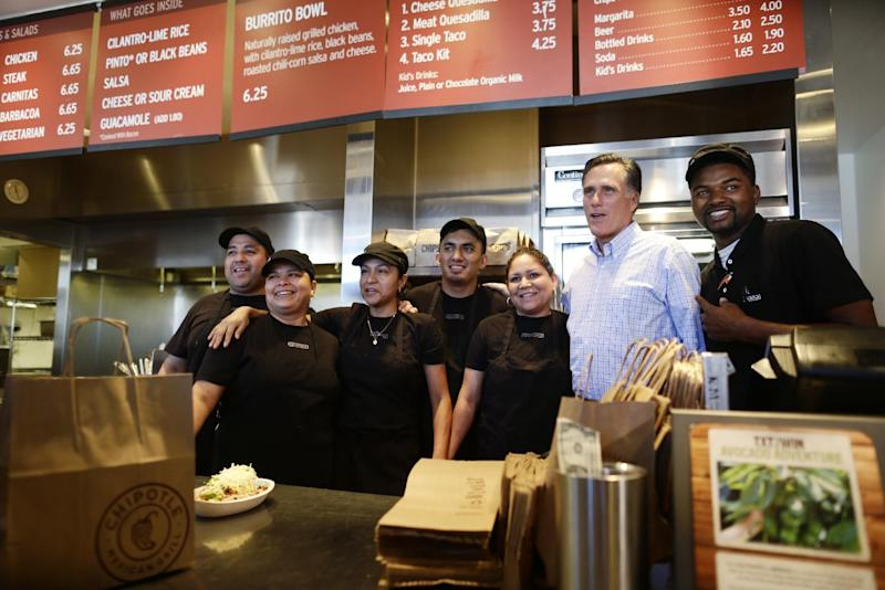 Republican presidential candidate, former Massachusetts Gov. Mitt Romney takes a photo with workers as he makes an unscheduled stop at a Chipotle restaurant in Denver, Tuesday, Oct. 2, 2012. (AP Photo/Charles Dharapak)