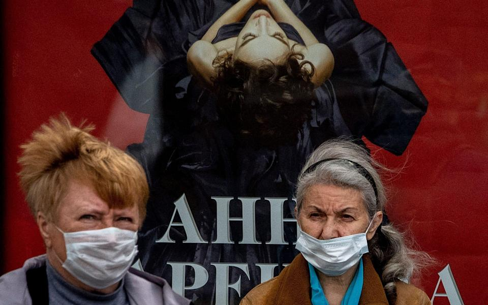Two women wearing face masks to protect against the coronavirus stand at a bus stop in Moscow - YURI KADOBNOV / AFP