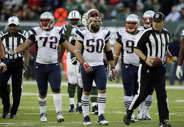 In this photo taken Sunday, Oct. 20, 2013, New England Patriots' Joe Vellano (72), Rob Ninkovich (50) and Chris Jones (94) watch as an official advances the ball after Jones was called for an unsportsmanlike penalty during overtime of an NFL football game against the New York Jets in East Rutherford, N.J. Jones was called for the penalty after pushing a teammate forward to try to block a Jets field goal, a new NFL rule. The Jets won the game 30-27 in overtime.(AP Photo/Seth Wenig)
