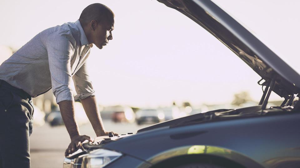 Mid adult black man analyzing his car after breakdown on the street.