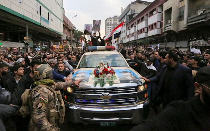 Mourners surround a car carrying the coffin of Iranian military commander Qassim Soleimani - AFP
